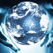 Glowing earth sphere in hands - Stock Photo