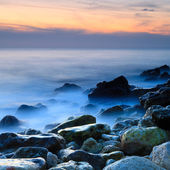 Seashore with misty water at sunset — Stock Photo