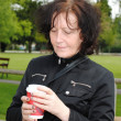 Mature woman drinking coffee in the park — Stock Photo #10690857