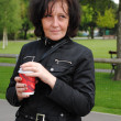 Mature woman drinking coffee in the park — Stock Photo #10690873