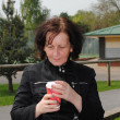 Mature woman drinking coffee in the park — Stock Photo