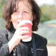 Mature woman drinking coffee in the park — Stock Photo #10690932