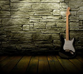 Grunge interior with electric guitar — Stock Photo