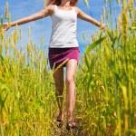 Beautiful young woman running through a wheat field — Stock Photo #8639657