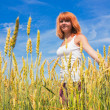 Beautiful young woman walking at wheat field — Stock Photo #8664966