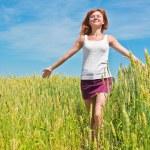Beautiful young woman running through a wheat field — Stock Photo #8751146