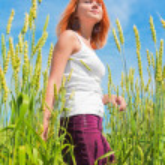 Beautiful young woman at wheat field — Stock Photo