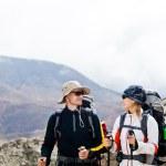 man en vrouw wandelen in de bergen — Stockfoto