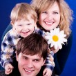 Beautiful young family with baby boy and flower — Stock Photo