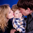 Family with baby boy on blue background — Stock Photo