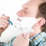 Portrait of mature handsome man shaving his beard — Stock Photo #10197305