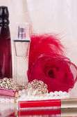 Parfum flessen rode lippenstift, veren, rose en parels parels — Stockfoto