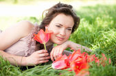 Beautiful woman with red spring tulips in a garden — Stock Photo