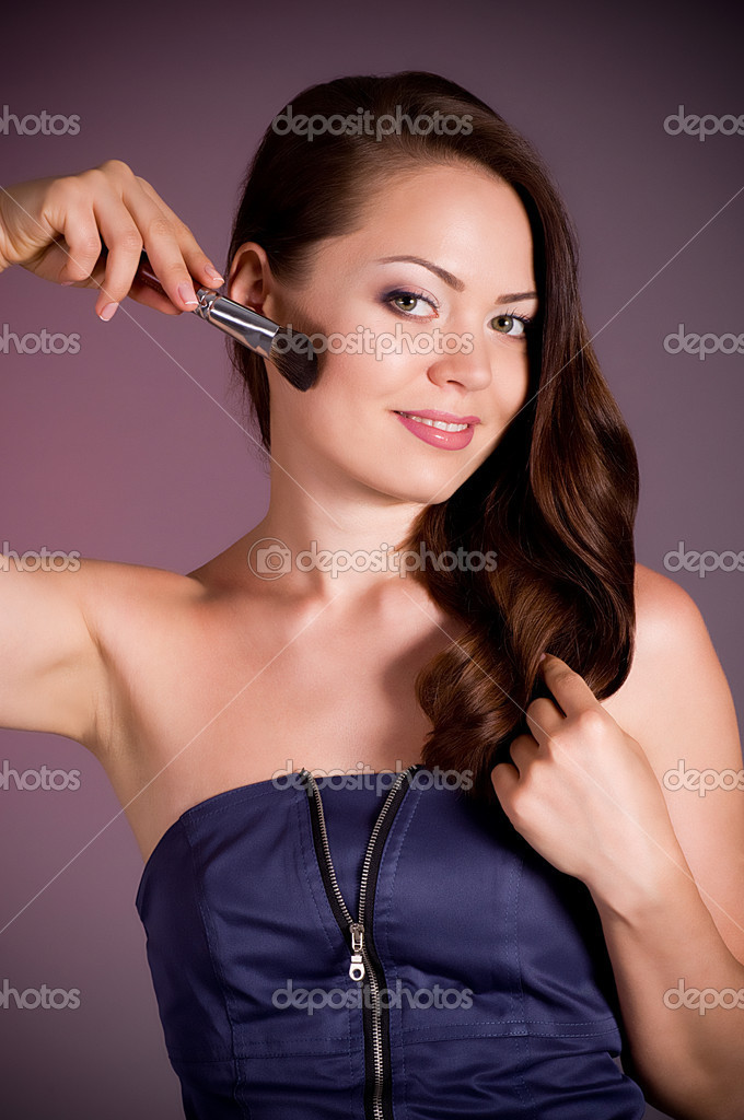 Beautiful woman applying makeup on face on dark background — Stock Photo #10518576
