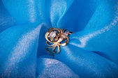 Golden jewelry ring on blue background — 图库照片