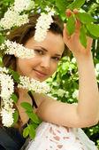 Krásná žena v jarní bílé květy — Stock fotografie