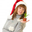 Woman in Santa Claus clothes holding a small plant — Stock Photo #8324509