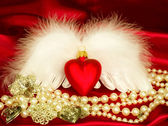 Valentine heart with wings on red background — Stock Photo