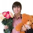 Young man with flowers and teddy bear - Stock Photo