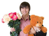 Young man with flowers and teddy bear — Stock Photo