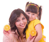Girl and her mother with orange — Stock Photo