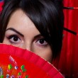 Beautiful young woman with red Asian fan — Stock Photo #8842079