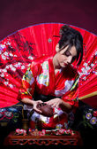 Woman in red Asian costume arranging Japanese tea ceremony — Stock Photo