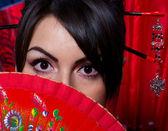 красивая молодая женщина с красной азиатских вентилятором — Стоковое фото