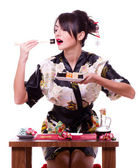 Woman in Japanese kimono with chopsticks and sushi roll — Stock Photo