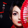 Woman in Asian costume with red Asian fan — Stock Photo