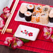 Stock Photo: Set of sushi rolls on the white plate with flowers