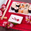 Set of sushi rolls on the white plate with flowers — Stock Photo