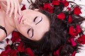 Beautiful sexy girl with rose petal in hears. Studio shot. — Stock Photo