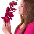 Beautiful young girl with orchid on white background. — Stock Photo