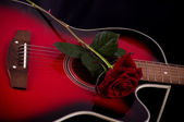 Beautiful red guitar with red roses — Stock Photo