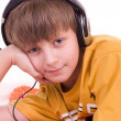 Little smiling boy listening to music in headphones - Stock Photo