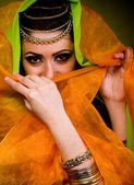 Beautiful young woman in color arabian clothes — Stock Photo