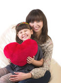 Mother and her little daughter embracing with red heart — Stock Photo