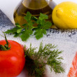 Piece of a salmon with lemon, tomato and olive oil — Stockfoto