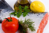 Piece of a salmon with lemon, tomato and olive oil — Stock Photo