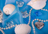Beautiful exotic shell and stones, pearls on blue background — Stock Photo