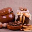 Stock Photo: Tasty jam, cupcakes, clay pot and nuts on background