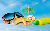 Shell, glasses, starfish and sun lotion on sand — Stock Photo