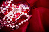 Bright colorful stones and pearl in heart — Stock Photo