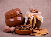 Tasty jam, cupcakes, clay pot and nuts on background — Стоковое фото