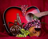 Beautiful composition with wine, grape and guitar on red background — Stock Photo