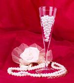 White flower, pearls and beads on red background — Stock Photo