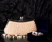 Sexy fashionable handbag with pearl jewelry on black background. — Stock Photo