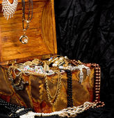 Old wooden open chest with golden jewelry — Стоковое фото