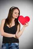 Beautiful young woman with red heart — Stock Photo